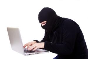 pirate informatiqye en cagoule devant son ordianteur